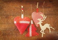 Kerstmisbeeld van stoffen rode harten en boom houten rendier en slingerlichten, die op kabel voor houten achtergrond hangen Stock Foto