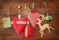 Kerstmisbeeld van stoffen rode harten en boom houten rendier en slingerlichten, die op kabel voor houten achtergrond hangen Stock Afbeeldingen