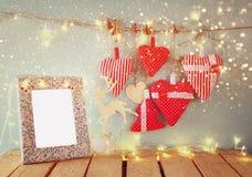 Kerstmisbeeld van stoffen rode harten en leeg kader, slingerlichten, die op kabel voor blauwe houten achtergrond hangen stock afbeeldingen
