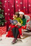 Kerstmisboek van de moederlezing aan haar jong geitje stock foto