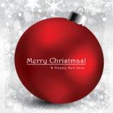 Kerstmisbol op grijze achtergrond met sneeuw Stock Afbeelding