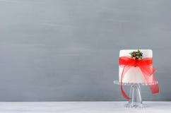 Kerstmiscake met maretak en rood lint op grijze B wordt verfraaid die Royalty-vrije Stock Afbeeldingen