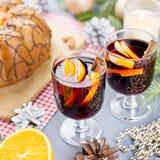 Kerstmiscake, twee glazen hete overwogen wijn met gesneden sinaasappel Kerstmisachtergrond met voedsel en decoratie stock fotografie