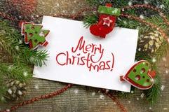 Kerstmisdecor met Witboek met een inschrijving van Vrolijke Kerstmis Stock Foto