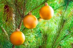 Kerstmisdecoratie, drie gouden ballen die op Kerstboom hangen royalty-vrije stock afbeeldingen