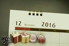 Kerstmisdecoratie en giftvakjes met kalenderpagina van maand Stock Fotografie