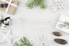 Kerstmisdecoratie, gift, berijpte ciprestakken, denneappels Houten achtergrond Royalty-vrije Stock Fotografie