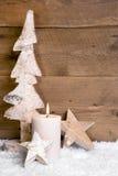 Kerstmisdecoratie: houten boom, sterren, kaars en sneeuw op houten Stock Foto's