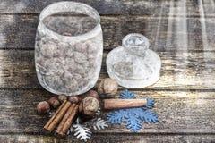 Kerstmisdecoratie, kaneel, kruik met vorst en noten, okkernoten, hazelnoten Gestemd beeld Getrokken sneeuw Royalty-vrije Stock Foto