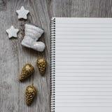 Kerstmisdecoratie, Kerstman` s witte laars, gouden sparappel, sneeuwvlokken en een open leeg notitieboekje, houten achtergrond Stock Fotografie