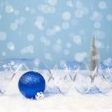 Kerstmisdecoratie met een blauwe bal, gebogen lint op bokehbedelaars Stock Afbeeldingen