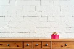 Kerstmisdecoratie met een gift op een oude plank op de achtergrond van een bakstenen muur stock afbeelding