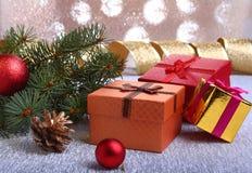 Kerstmisdecoratie met giftdozen, kleurrijke Kerstmisballen, Kerstmisboom en kegels op onscherp, fonkelend en Stock Foto