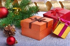 Kerstmisdecoratie met giftdozen, kleurrijke Kerstmisballen, Kerstmisboom en kegels op onscherp, fonkelend en Stock Afbeeldingen