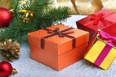 Kerstmisdecoratie met giftdozen, kleurrijke Kerstmisballen, Kerstmisboom en kegels op onscherp, fonkelend en Royalty-vrije Stock Foto