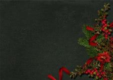 Kerstmisdecoratie met hulst en poinsettia op dark Stock Foto's