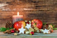 Kerstmisdecoratie met kaarslicht, sterkoekjes, rode appelen, noten en kruiden stock afbeeldingen