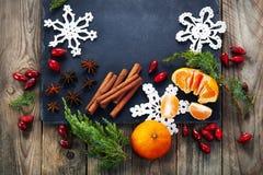 Kerstmisdecoratie met mandarijn, heupen, kaneel op donkere uitstekende achtergrond Royalty-vrije Stock Fotografie