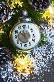 Kerstmisdecoratie met retro stuk speelgoed van wekkerkerstmis, denneappels en slingerlichten op oude houten achtergrond Vrolijke  Royalty-vrije Stock Foto