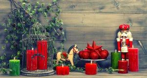 Kerstmisdecoratie met rode kaarsen en uitstekend speelgoed Stock Foto