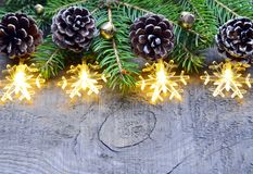 Kerstmisdecoratie met slingerlichten, denneappels en spar op oude houten achtergrond De grens van Kerstmis De wintervakantie conc Stock Foto