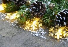 Kerstmisdecoratie met slingerlichten, denneappels en spar op oude houten achtergrond Het concept van de de wintervakantie Royalty-vrije Stock Fotografie