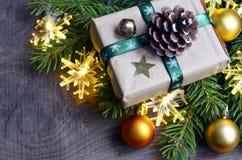Kerstmisdecoratie met spar, giftdoos, slingerlichten en Kerstmisballen op oude houten achtergrond Royalty-vrije Stock Fotografie