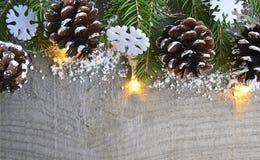 Kerstmisdecoratie met spar, slingerlichten en denneappels op grijze houten achtergrond Stock Fotografie