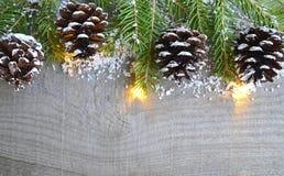 Kerstmisdecoratie met spar, slingerlichten en denneappels op oude houten achtergrond Het concept van de de wintervakantie Stock Foto