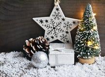 Kerstmisdecoratie met spar, slingerlichten, giftdoos, en schitterende Kerstmisbal op oude houten achtergrond Stock Foto's