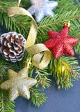 Kerstmisdecoratie met sparrentak, glanzende Kerstmissterren, gouden lint en denneappel op een donkere achtergrond Stock Fotografie