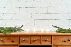 Kerstmisdecoratie met takjes op een oude plank op de achtergrond van een bakstenen muur royalty-vrije stock afbeelding