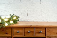 Kerstmisdecoratie met takjes van sparren en lihgts op een plank op de achtergrond van een bakstenen muur royalty-vrije stock foto