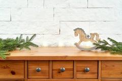 Kerstmisdecoratie met takjes van sparren en paard op de plank op de achtergrond van een bakstenen muur royalty-vrije stock foto