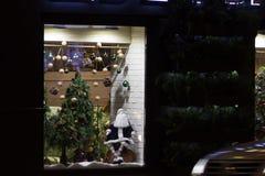 Kerstmisdecoratie op een winkelvenster De pop van de Kerstman, Kerstmisboom met glasballen en pinecones royalty-vrije stock fotografie