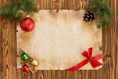 Kerstmisdecoratie op het oude blad van document op een houten rug Stock Foto's