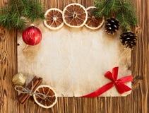 Kerstmisdecoratie op het oude blad van document op een houten rug Royalty-vrije Stock Fotografie