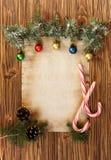 Kerstmisdecoratie op het oude blad van document op een houten rug Royalty-vrije Stock Foto's