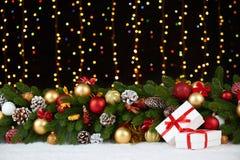 Kerstmisdecoratie op wit bont met de close-up van de sparrentak, giften, Kerstmisbal, kegel en ander voorwerp op donkere achtergr Stock Afbeelding