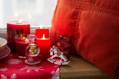Kerstmisdecoratie: suikergoed, speelgoed, hoofdkussen en brandende rode kaarsen Stock Fotografie