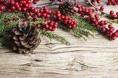 Kerstmisdecoratie van denneappel en rode winterberry Stock Afbeelding
