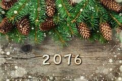 Kerstmisdecoratie van spar en naaldboomkegel op geweven houten achtergrond, magisch sneeuweffect en houten aantallen van Nieuw ja Royalty-vrije Stock Foto's