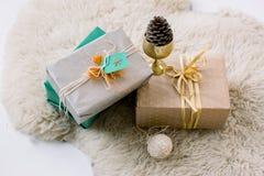 Kerstmisdozen met giften die op het bonttapijt liggen stock afbeelding