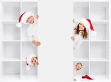 Kerstmisfamilie in de hoeden van de Kerstman met het opschorten Royalty-vrije Stock Foto's