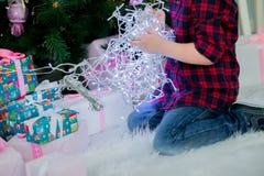 Kerstmisgerlyanda in de handen van een kind Stock Afbeeldingen