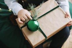 Kerstmisgift in de handen van kinderen Een kind die een verfraaide gift houden De decoratie van Kerstmis De winter, Nieuwjaar, Ke stock foto's