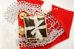 Kerstmisgift en ballen op santahoed Stock Foto's