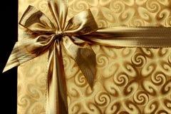 Kerstmisgift in gouden document met boog Achtergrond royalty-vrije stock afbeelding