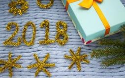 Kerstmisgift op een gebreide die achtergrond en cijfers van klatergoud wordt gemaakt Royalty-vrije Stock Afbeelding
