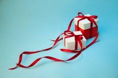 Kerstmisgift ` s in Witte Doos met Rood Lint op Lichtblauwe Achtergrond De nieuwe samenstelling van de jaarvakantie De ruimte van royalty-vrije stock foto
